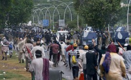 ?? — AP ?? Pakistani protesters chase police officers during clashes in Islamabad on Monday. The demonstrators pushed into a sprawling government complex in an effort to try to reach the Prime Minister's official residence.