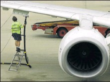 ?? File picture: REUTERS ?? GROUNDED: A staff member stands beside a fuel attachment to a Qantas plane at Sydney airport. Airlines are choosing not to refuel in Nigeria due to high jet fuel prices.