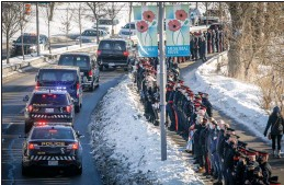 ?? CP PHOTO JEFF MCINTOSH ?? Police vehicles escort the body of Calgary Police Service Sgt. Andrew Harnett from the medical examiner's office to a funeral home as police officers and citizens line Memorial Drive in Calgary on Tuesday.