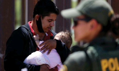 ?? Photograph: Jim Urquhart/Reuters ?? A man seeking asylum holds his infant daughter as they wait to be transported by the US Border Patrol after crossing from Mexico into California on 19 April.