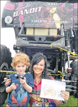 ?? JOE GIBBONS/THE TELEGRAM ?? Dawn Creten, driver of the monster truck Scarlet Bandit, poses with Liam Squires, 5, of Portugal Cove St. Philip's during a special visit by Creten and her husband Jimmy, who drives Bounty Hunter, Friday at the Janeway in St. John's.