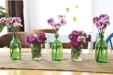 ??  ?? ANDREA SAVES small drink bottles and jars to be reused in a multitude of ways. Here they comprise a casual centerpiece of pink flowers. She says they're great to save for parties as an inexpensive way to decorate a large area.