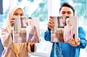 ?? - Bernama photo ?? Two models holding the two new cookbooks on Pahang traditiona­l dishes and desserts.