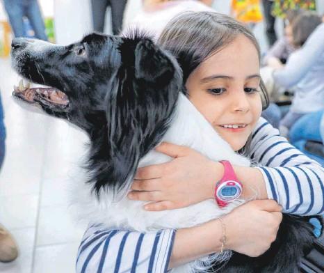 ?? FOTO: VADIM GHIRDA/DPA ?? Auch Tierkuscheln hilft: Ein Kind umarmt in einer Einrichtung für Kinder mit Downsyndrom in Rumänien einen speziell ausgebildeten Hund.