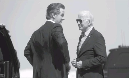?? LEAH MILLIS/REUTERS ?? California Gov. Gavin Newsom (D) speaks with President Biden as he arrives at Mather Airport in Mather, Calif., on Monday. In addition to campaigning for Newsom ahead of Tuesday's vote, he promoted coronavirus vaccinations.