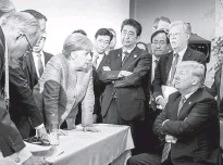 ?? JESCO DENZEL/AGENCE FRANCE-PRESSE/GETTY IMAGES ?? At the 2018 G-7 summit, Merkel leans over an intractable President Donald Trump as other world leaders look on.