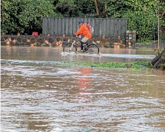 ?? PHOTO: JOHN KIRK-ANDERSON/STUFF ?? A cyclist pushes through floodwater in Christchurch's southern suburbs.