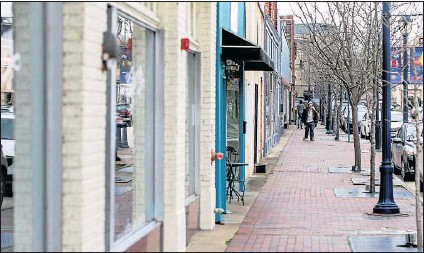?? PHOTOS BY DANIEL SANGJIB MIN/TIMES-DISPATCH ?? ABOVE: A pedestrian in Hopewell walks along East Broadway, where businesses have opened.