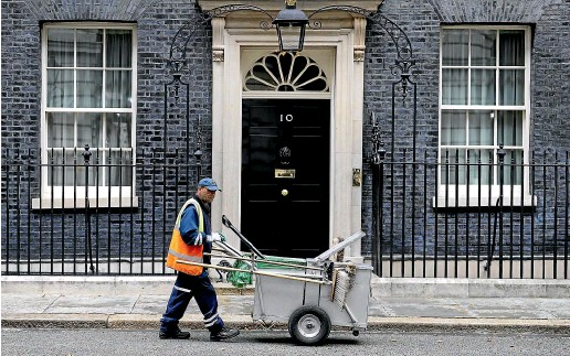 ??  ?? A street cleaner works outside No. 10 Downing Street, while inside Prime Minister Boris Johnson plans an exit from the EU regardless of British politics.