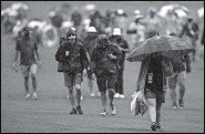 ?? MATT SLOCUM   Associated Press ?? RAINY DAY: Spectators leave the course after play is suspended for inclement weather in the third round.
