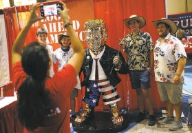 ?? Joe Raedle / Getty Images ?? Attendees of the Conservative Political Action Conference pose for photos with a golden statue of former President Donald Trump on display in Orlando.