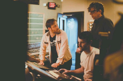 ?? PHOTOS: ALYSSE GAFKJEN ?? The Black Keys — Dan Auerbach, left, and Patrick Carney, behind right — are seen hard at work in a Nashville studio in 2019.