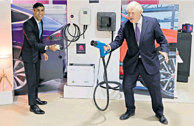 ?? − ?? Boris Johnson and Rishi Sunak demonstrate electric car charging points on a visit to the headquarters of Octopus Energy London start-up tech company which hopes to create 1,000 new jobs across the UK a