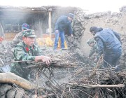?? XINHUA VIA AP ?? Chinese soldiers help people clear rubble from a damaged house following an earthquake in Kuzigun village in Taxkorgan County, Xinjiang, yesterday.