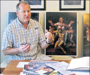 ?? AP PHOTO ?? Martin Kober displays literature and copies of a family heirloom that he believes was painted by Renaissance master Michelangelo, at his home in Tonawanda, N.Y. Kober is convinced the painting of a dying Jesus that hung above the mantel in his upstate...