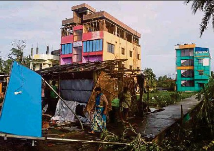 ?? AFP PIC ?? Villagers walking past debris after Cyclone Bulbul hit Bakkhali area in West Bengal, India yesterday.