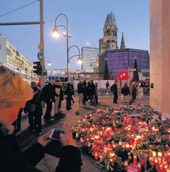 ?? Sean Gallup ?? > Mourners lay flowers and candles at a makeshift memorial near the site where a man drove a lorry into a Christmas market in Berlin, killing 12 people and injuring 48