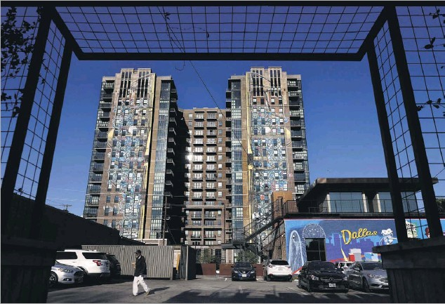 ?? Photos by Tom Fox/staff Photographer ?? Large bright art murals run down length of the Case Building apartment tower, at 3131 Main St. in Deep Ellum in Dallas.