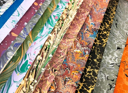??  ?? A range of finished sheets of paper, with swirls, scallops, marble and feathery designs in an explosion of colours.