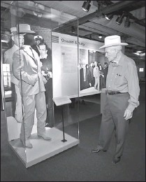 ??  ?? This undated photo provided by The Sixth Floor Museum at Dealey Plaza in Dallas shows retired Dallas Police Detective Jim Leavelle viewing the tan-colored suit he was wearing when Lee Harvey Oswald was shot.