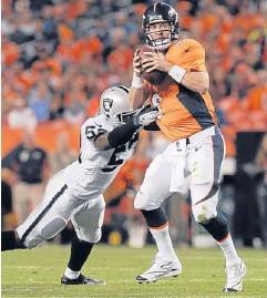 ?? AP ?? The Broncos' Peyton Manning scrambles away from Raiders linebacker Nick Roach.