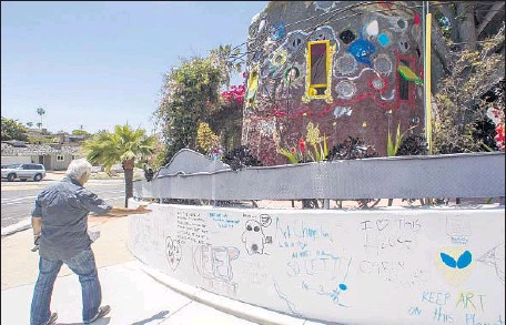 """?? Photographs by John Gibbins San Diego Union-Tribune ?? THE WALL around La Jolla artist Nasser Pirasteh's home is full of messages from people supporting his vivid sculpture, titled """"In Out."""""""