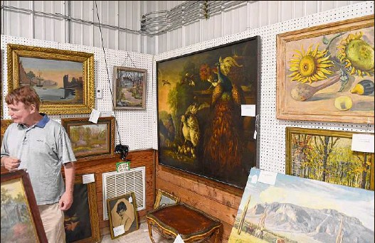?? Will Waldron / Times Union ?? Antiques dealer Robert Meringolo displays paintings and antiques from the estate of Fort Plain resident Paul Verbitsky on Monday at Mooney's Auction House in Freehold. The collection has 800 paintings from old masters to modern and goes up for auction on Saturday.