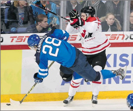 ?? — THE CANADIAN PRESS ?? Canada's Jake Virtanen tries to knock Finland's Juho Lammikko off the puck during first-period action on Saturday. Canada dropped a disappointing 6-5 game to Finland.