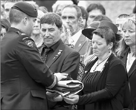 ?? PHOTO PC ?? √ Un des moments les plus touchants de la cérémonie : la remise du drapeau canadien ainsi que les médailles et le béret du soldat à la mère du soldat, Monique Chevrier, et son père, Jacques Péloquin.