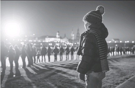 ?? SEAN GALLUP/GETTY IMAGES ?? People link hands Friday as they stand along the Elbe River, across from Dresden's historic city centre, to commemorate the 70th anniversary of the Allied firebombing of the city by U.S. and British forces. An estimated 25,000 people were killed.
