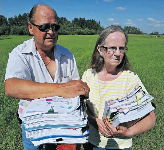 ?? ED KAISER- EDMONTON JOURNAL ?? Barb and Rick Bilozer with some of the paperwork concerning their battle with Imperial Oil over remediation of their land. They have been fighting to have the family farm cleaned up after it was contaminated by Imperial Oil in the 1980s.