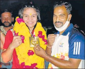 ?? HT PHOTO ?? Arundhiti Chaudhary being greeted by family members on her arrival in Kota after winning gold in 69 kg weight category of boxing at the Youth World Boxing Championship in Poland.