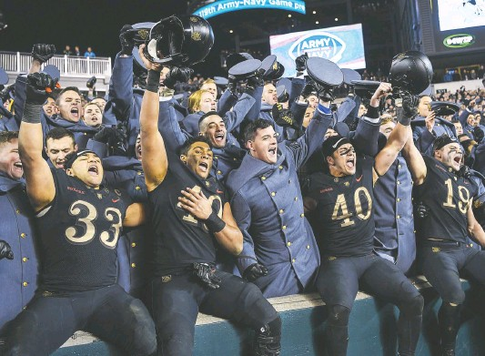 ?? JONATHAN NEWTON/THE WASHINGTON POST ?? Army football players celebrate with the Corps of Cadets after their third consecutive win over rival Navy on Saturday night at Philadelphia's Lincoln Financial Field.