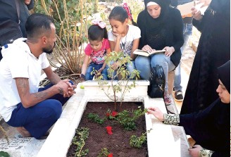 ??  ?? Members of Khaled's family gather around the boy's grave 40 days after his death.