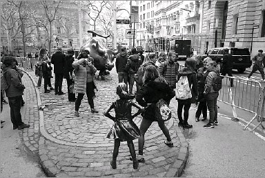 ?? Mark Lennihan/The Associated Press ?? The 4-foot girl, hands planted on her hips and staring down the 11-foot bull, quickly became a tourist magnet, drawing global attention on social media while awakening the imaginations of visitors who posed for pictures.