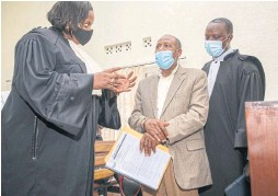 ??  ?? Paul Rus­esabag­ina, hand­cuffed, dis­cusses his case with two lawyers he picked from a list supplied by the gov­ern­ment in Ki­gali.