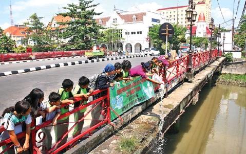 ?? AHMAD KHUSAINI/JAWA POS ?? BIAR BERKEMBANG: Anak-anak SDN Bubutan IV melepas ikan lele ke Kalimas dari Jembatan Merah.