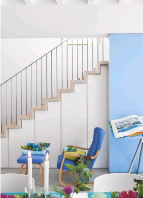 ??  ?? STAIRCASE Blue and white tones enhance the open, airy feel. Vintage armchair and footstool upholstered in Brera Lino linen in Cobalt, Designers Guild. Limited edition Tripod bookstand by Marc Newson for Taschen, displaying David Hockney's A Bigger Book (Taschen)