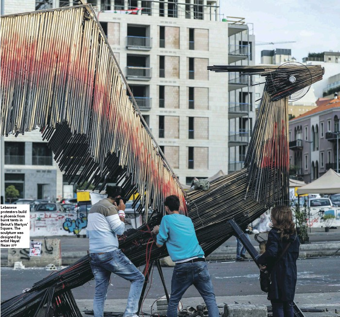 ?? AFP ?? Le­banese pro­test­ers build a phoenix from burnt tents in Beirut's Mar­tyrs' Square. The sculp­ture was de­signed by artist Hayat Nazer