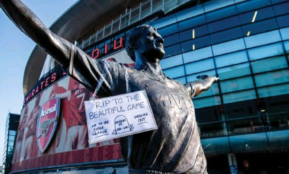 ?? Photograph: Jill Mead/The Guardian ?? A sign condemning the Super League is placed on a statue of Tony Adams outside Arsenal's Emirates stadium.