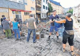 ?? REUTERS ?? People remove debris and rubbish following heavy rainfalls in Bad Muenstereifel, North RhineWestphalia state, Germany.