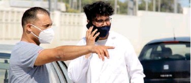 ?? Associated Press ?? ↑ Tunisians, wearing face masks, stand outside a hospital in Tunis on Wednesday.