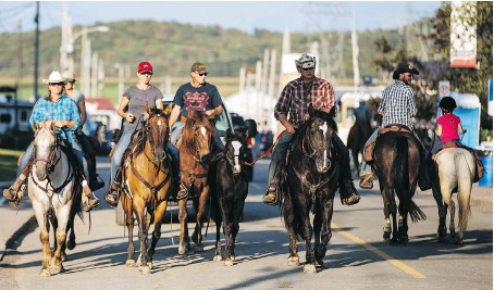 ?? PHOTOS: DARIO AYALA/MONTREAL GAZETTE ?? People ride horses through the street during the Western Festival in St-Tite, a rural Quebec town about 180 kilometres east of Montreal.