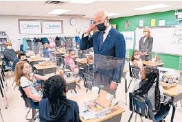 ?? MANDEL NGAN/GETTY-AFP ?? President Joe Biden points to his hair after a student told him she wanted to be a hairdresser during his visit Monday to a Yorktown, Virginia, elementary school.