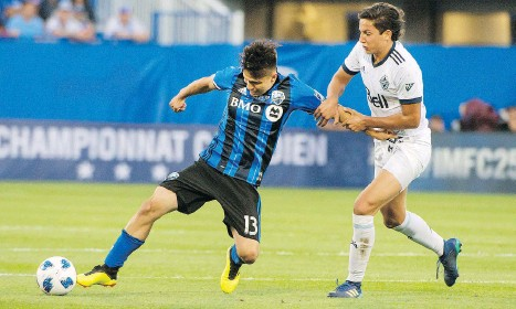 ?? PETER MCCABE/THE CANADIAN PRESS ?? Montreal Impact's Ken Krolicki, left, tangles with Vancouver Whitecaps' David Norman Jr. during first-half Canadian Championship action in Montreal on Wednesday. The Impact's Alejandro Silva got the game's only goal in the 58th minute.
