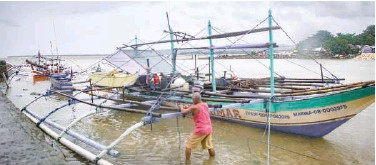 ?? Agence France-presse ?? ↑ A fisherman secures his boat along the seashore of Borongan in Samar in preparation of Typhoon Surigae on Sunday.