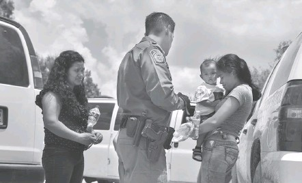 ?? JAHI CHIKWENDIU/THE WASHINGTON POST ?? Two Honduran mothers are detained by a Border Patrol officer in Texas after rafting the Rio Grande on the U.S.-Mexico border. Trump has touted record arrests at the southern border after previously deriding former administrations for their supposed increases.