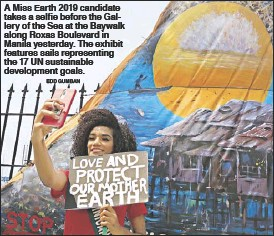 ?? EDD GUMBAN ?? A Miss Earth 2019 candidate takes a selfie before the Gallery of the Sea at the Baywalk along Roxas Boulevard in Manila yesterday. The exhibit features sails representing the 17 UN sustainable development goals.