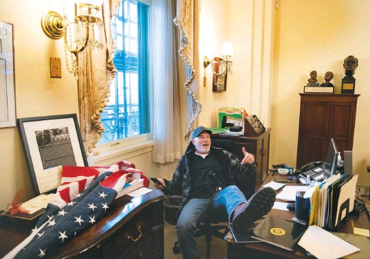 ?? SAUL Loeb/agence FRANCE-PRESSE/GETTY IMAGES ?? Richard Barnett, a 60-year-old Arkansan pictured with his feet on a staffer's desk in House Speaker Nancy Pelosi's office, has been charged for his role in storming the Capitol building on Wednesday. Barnett, below in Arkansas, told the New York Times that he had just been knocking on the door when he was pushed in by the crowd.