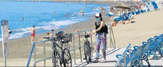 ?? JAVIER ALBIÑANA ?? Una mujer llega a la playa en bicicleta.